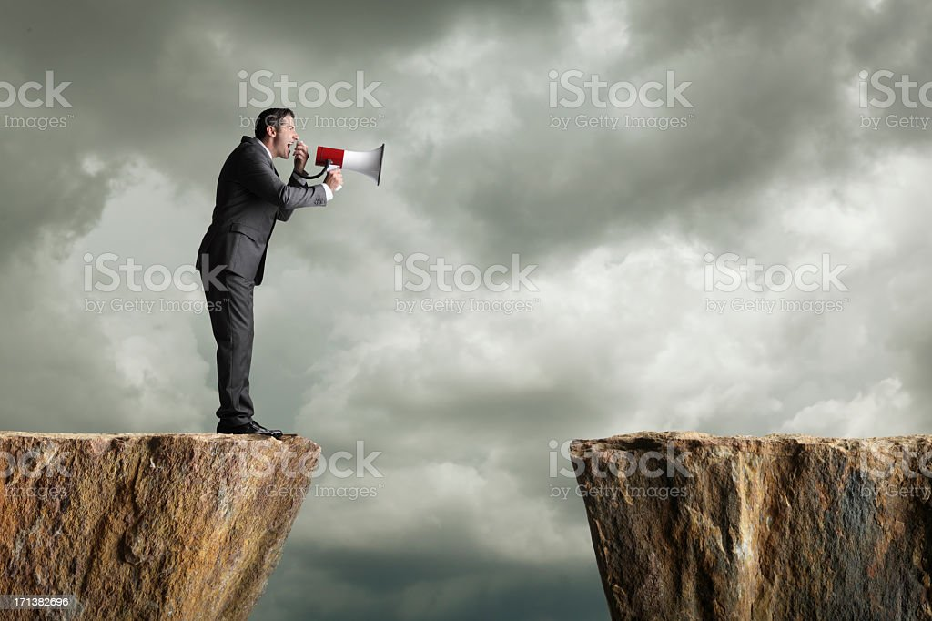 Businessman standing on a cliff shouting into a megaphone stock photo