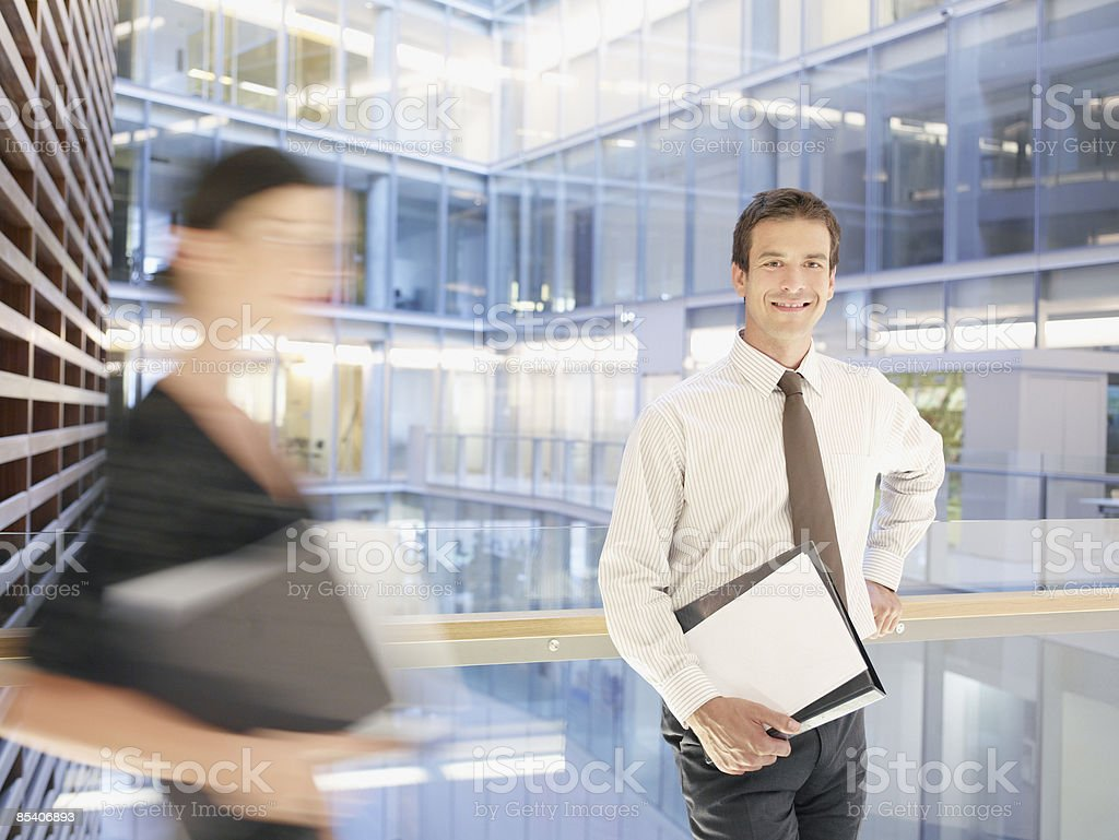 Businessman standing on atrium balcony royalty-free stock photo