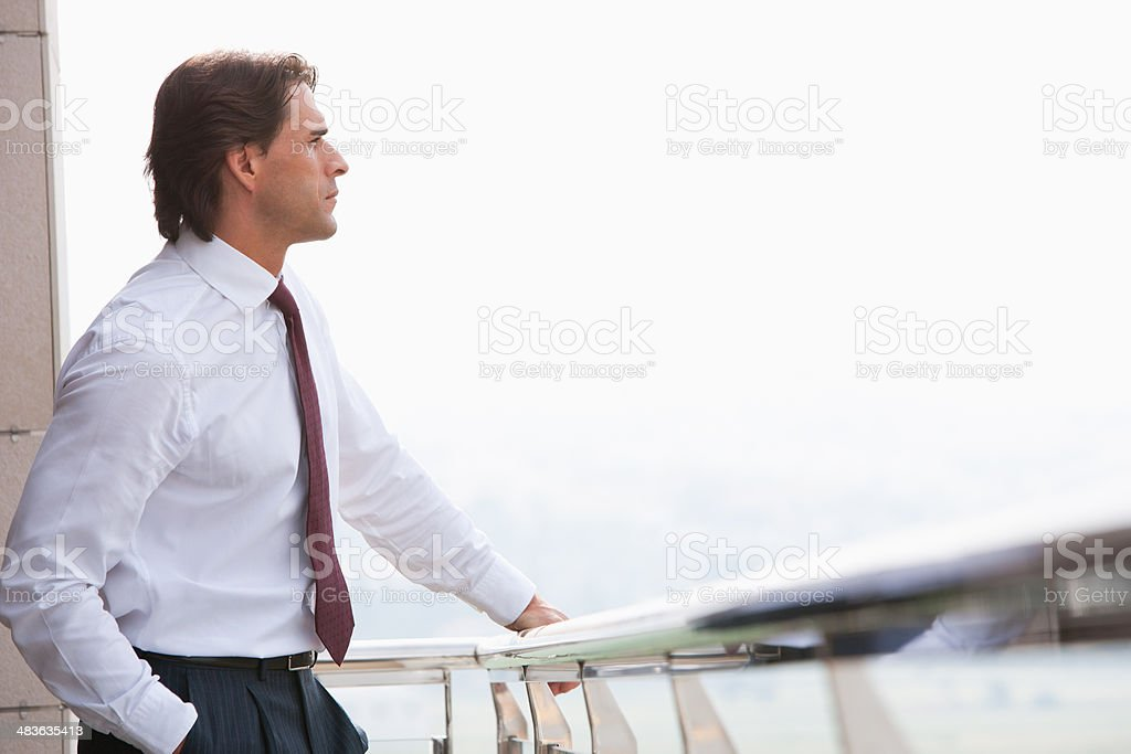 Businessman standing on balcony  stock photo