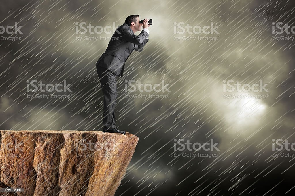 Businessman standing on cliff in driving rain looking through binoculars stock photo