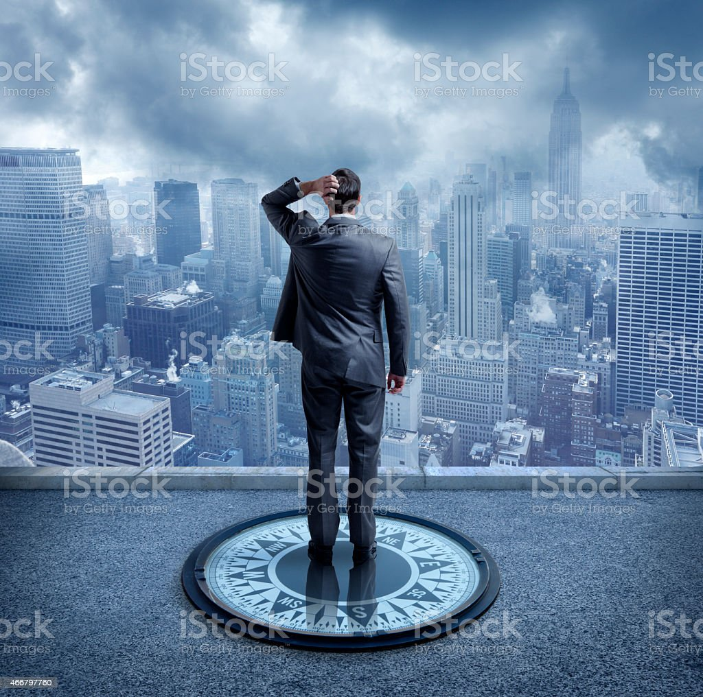 Businessman standing on compass looking at New York City stock photo