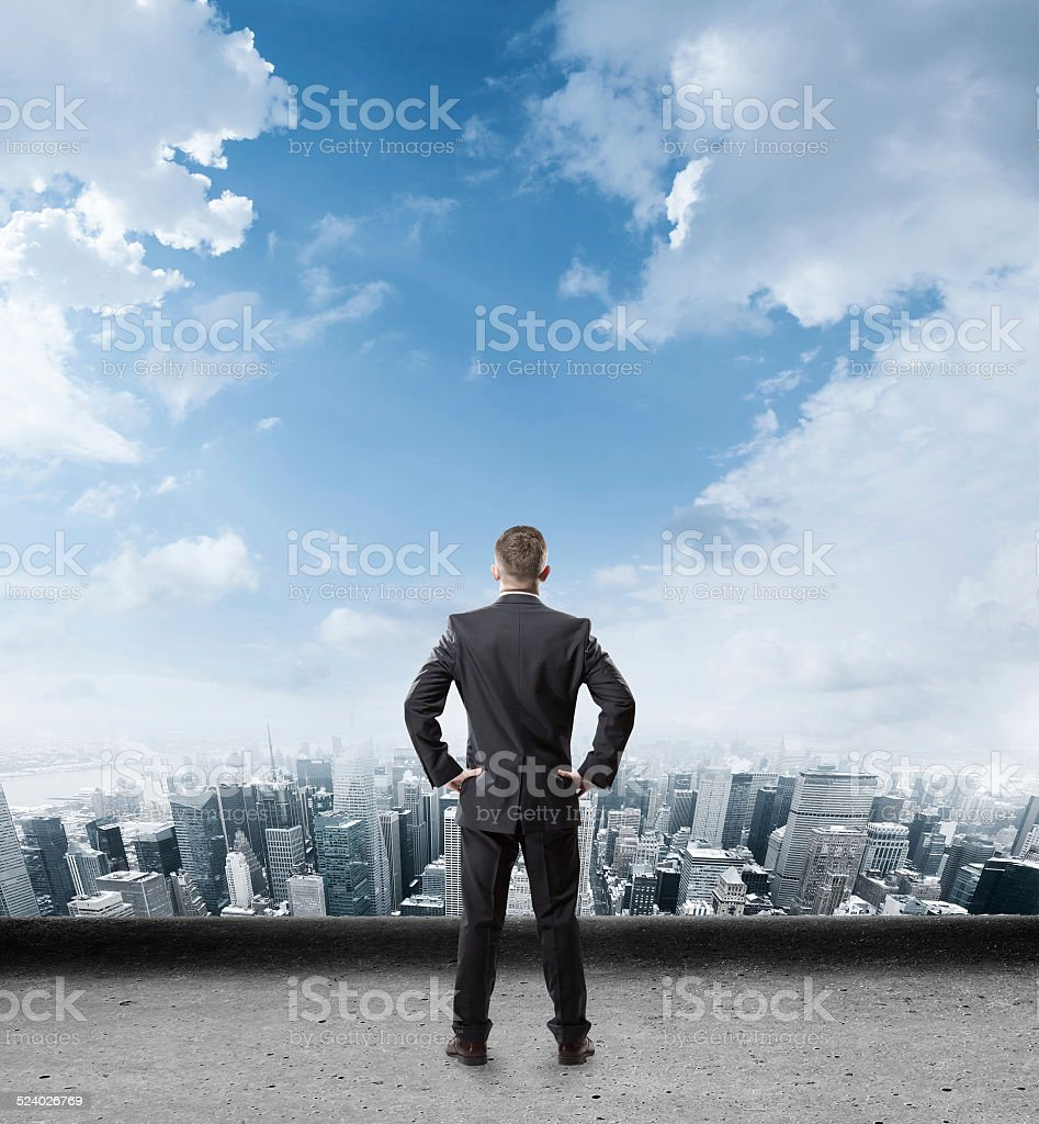 businessman standing on edge and looking into the city stock photo