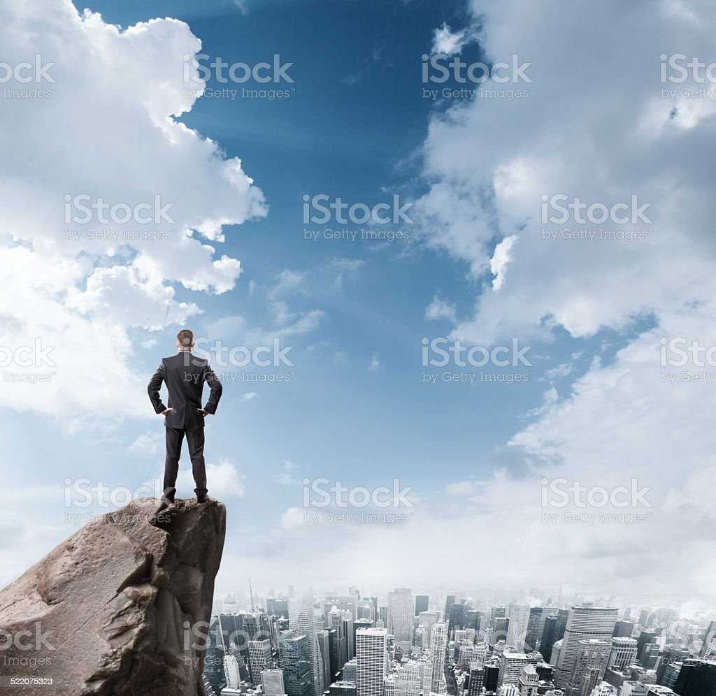 businessman standing on edge of rock mountain stock photo