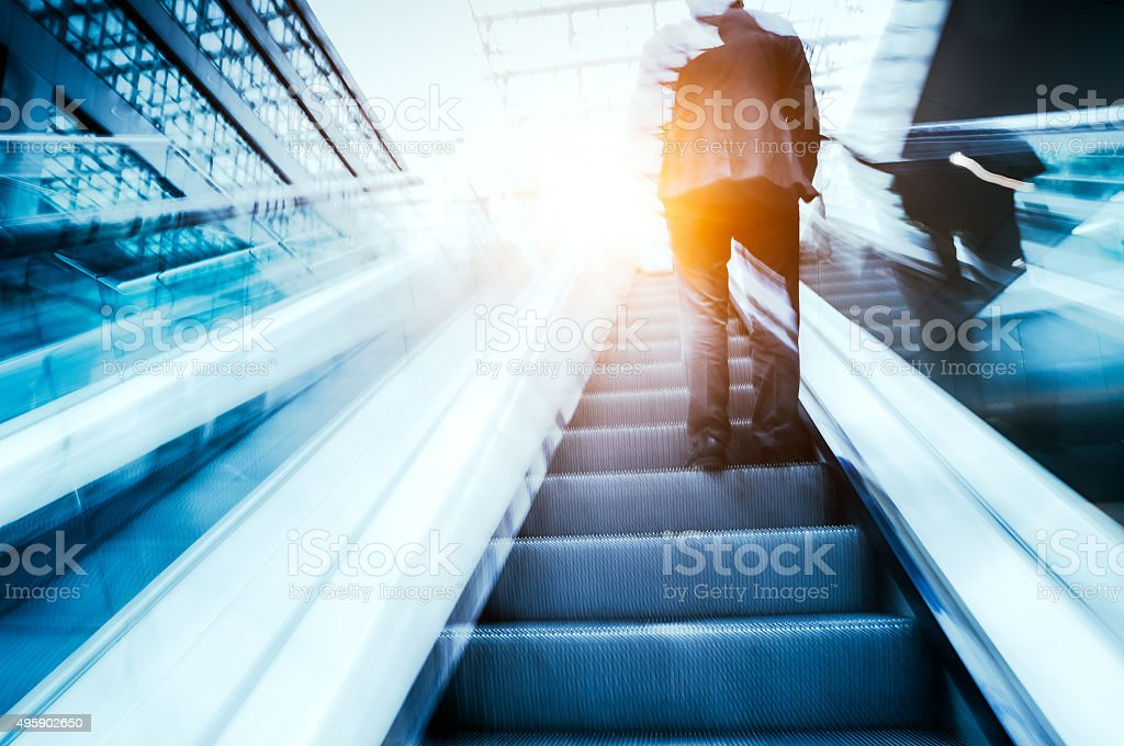 Businessman standing on escalator stock photo