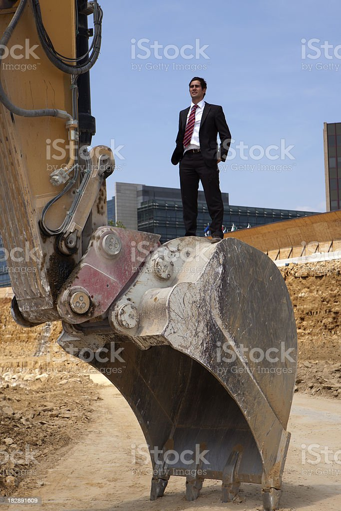 Businessman standing on excavator royalty-free stock photo