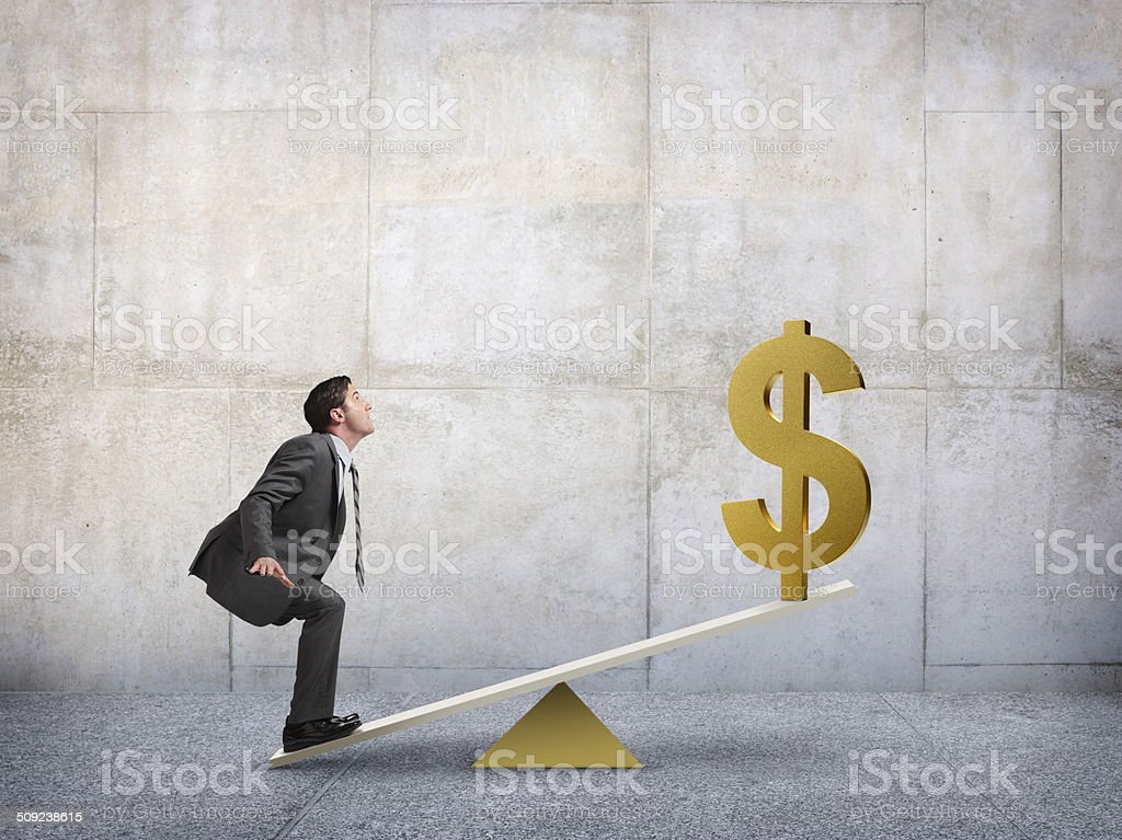 Businessman standing on fulcrum using financial leverage stock photo