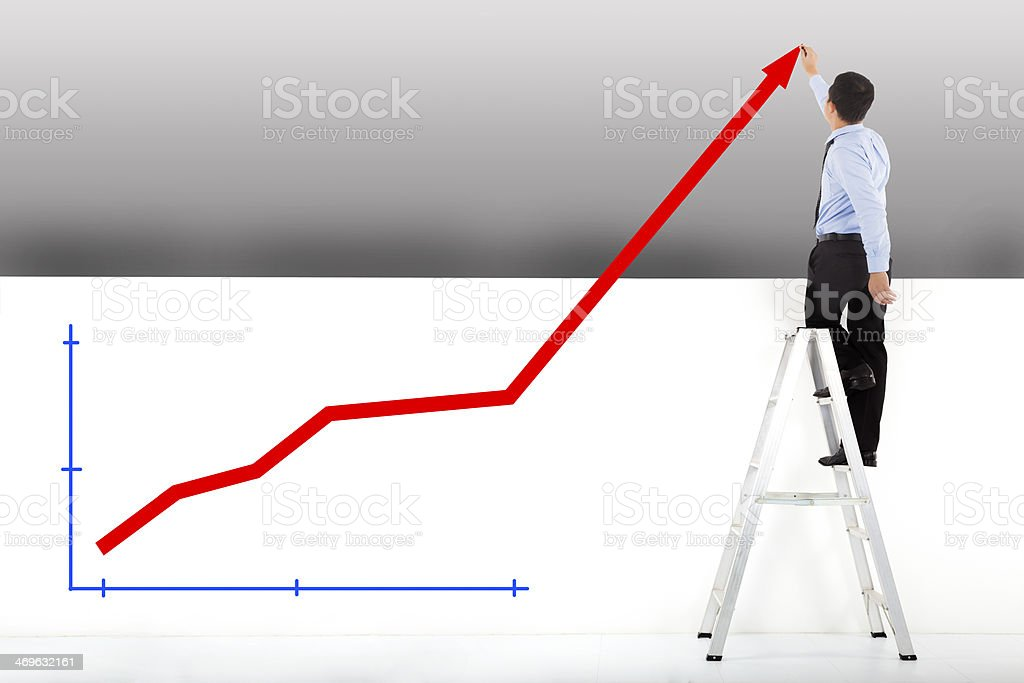 businessman standing on ladder drawing diagrams royalty-free stock photo