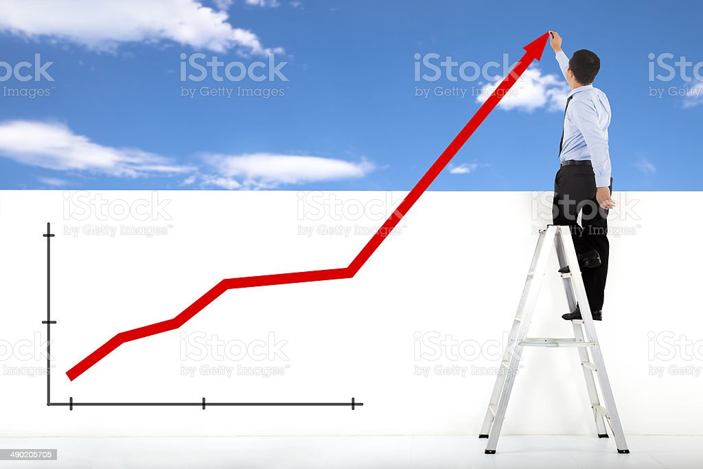 businessman standing on ladder drawing global diagrams stock photo