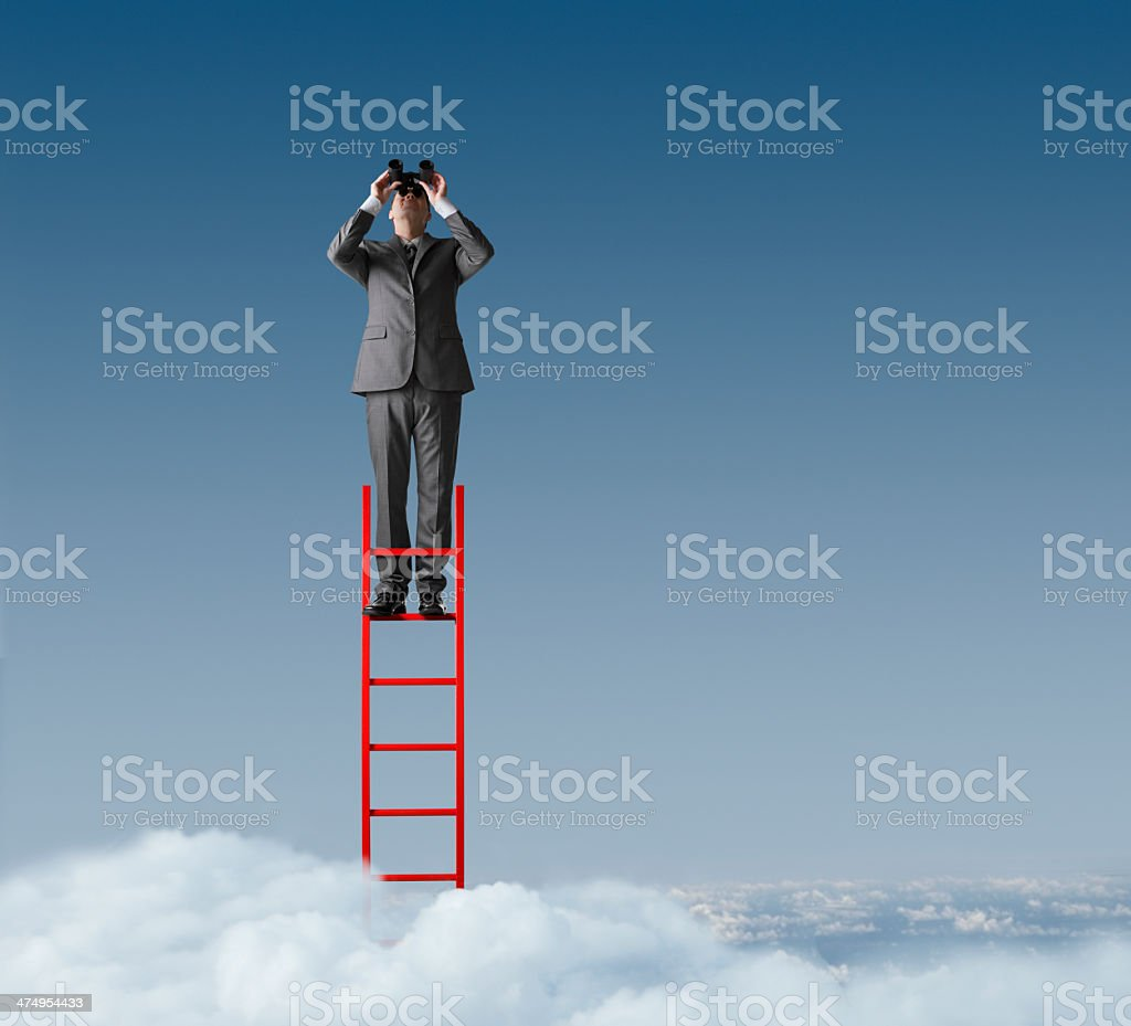 Businessman standing on ladder looking through binoculars stock photo