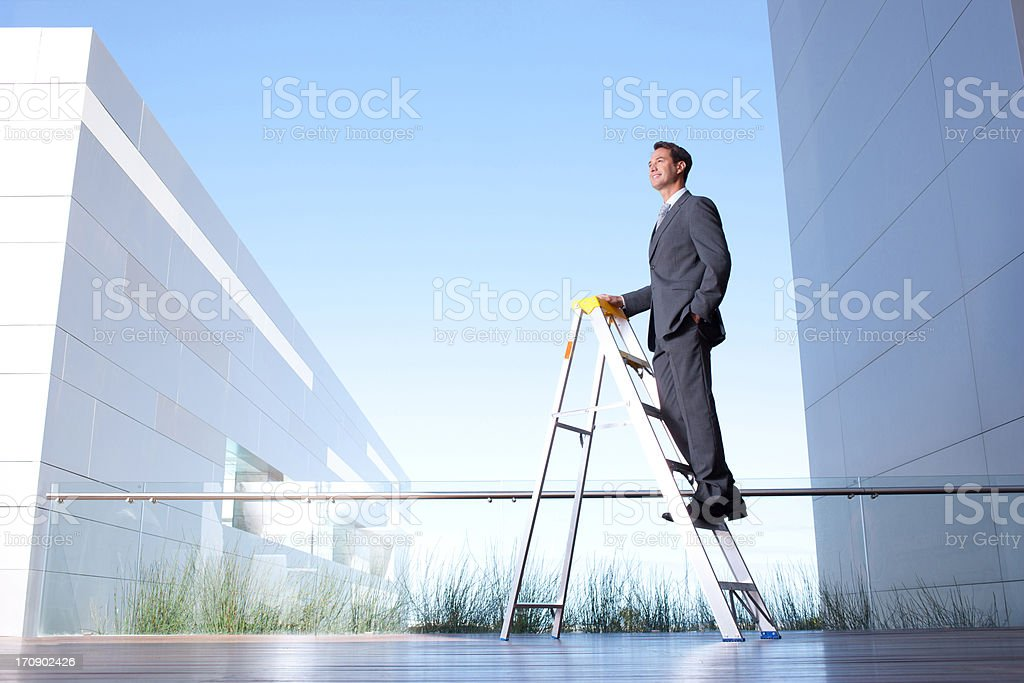 Businessman standing on ladder on balcony royalty-free stock photo