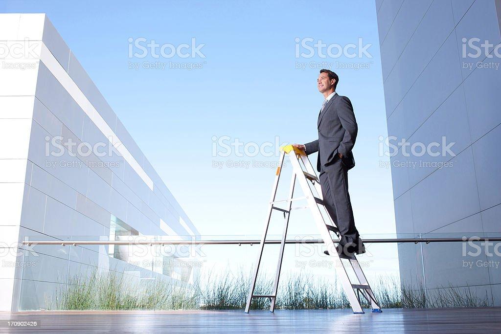 Businessman standing on ladder on balcony stock photo