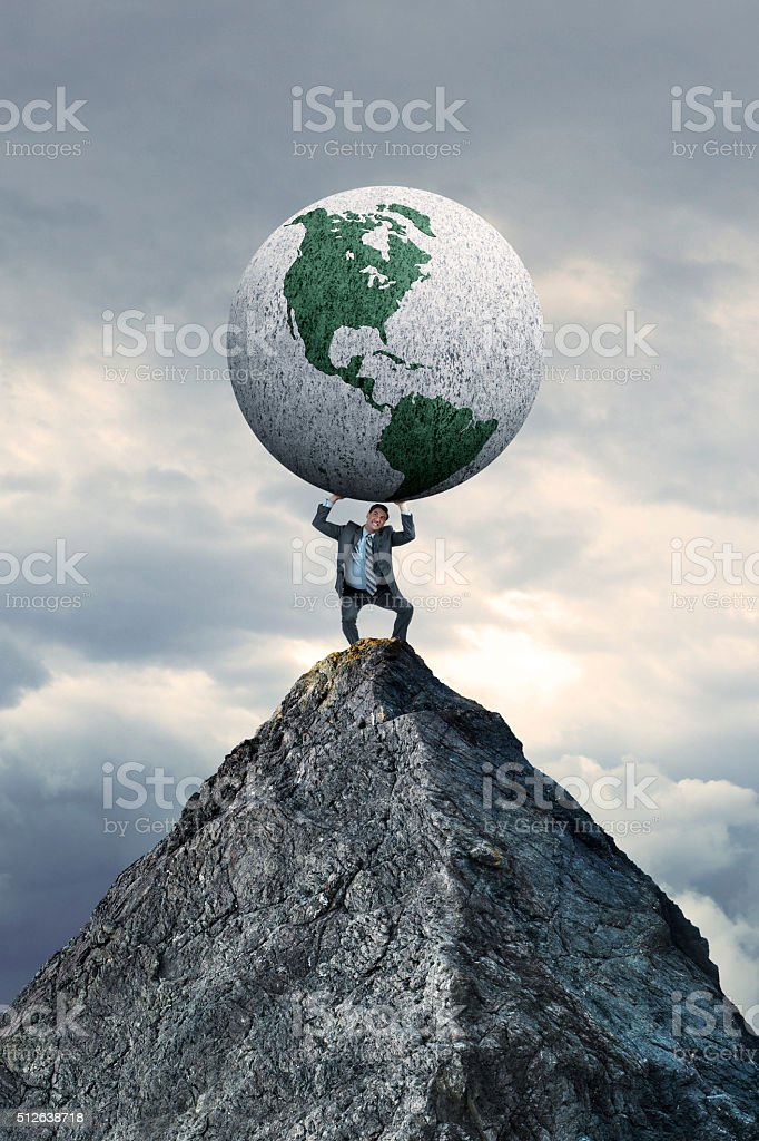 Businessman Standing On Mountain Top Holding A Globe stock photo