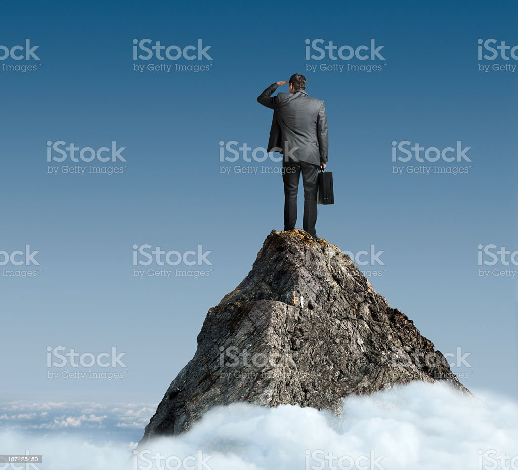 Businessman standing on mountaintop looking into distance royalty-free stock photo
