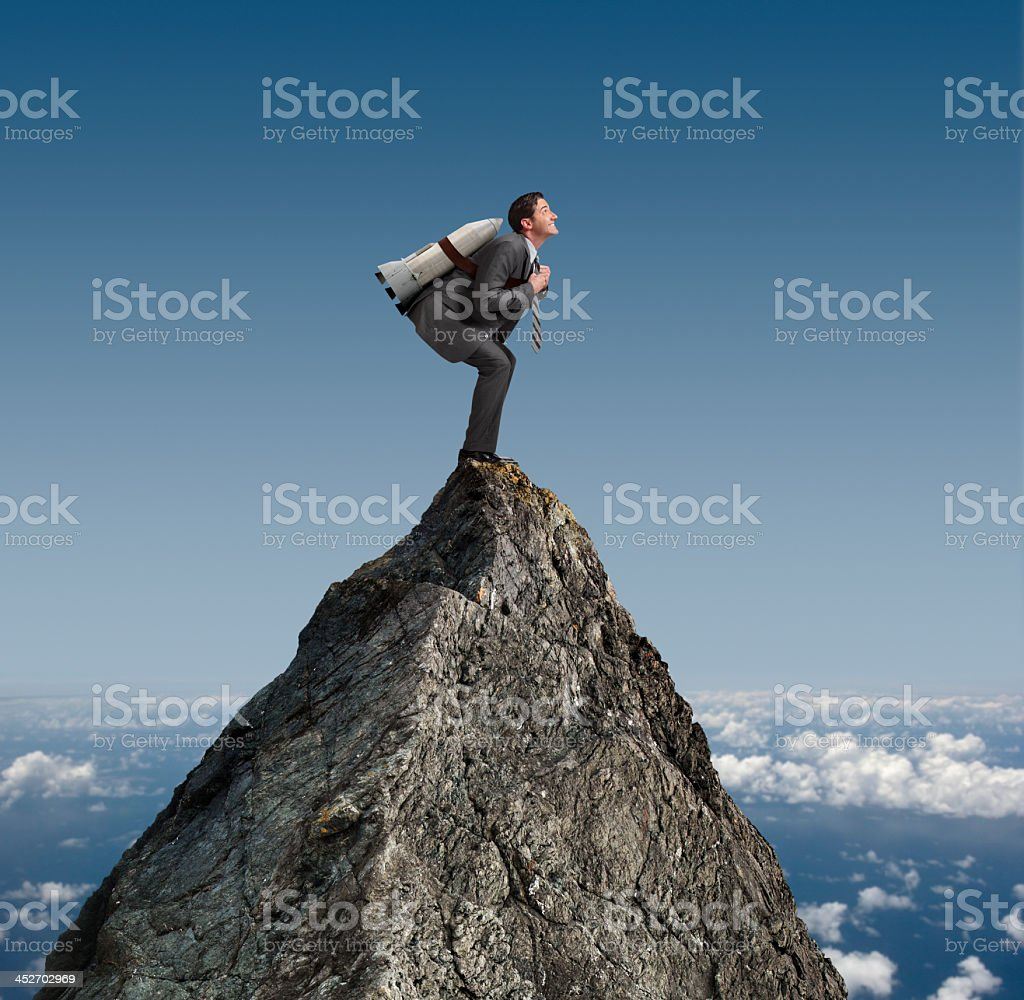 Businessman standing on mountaintop with rocket strapped to his back stock photo