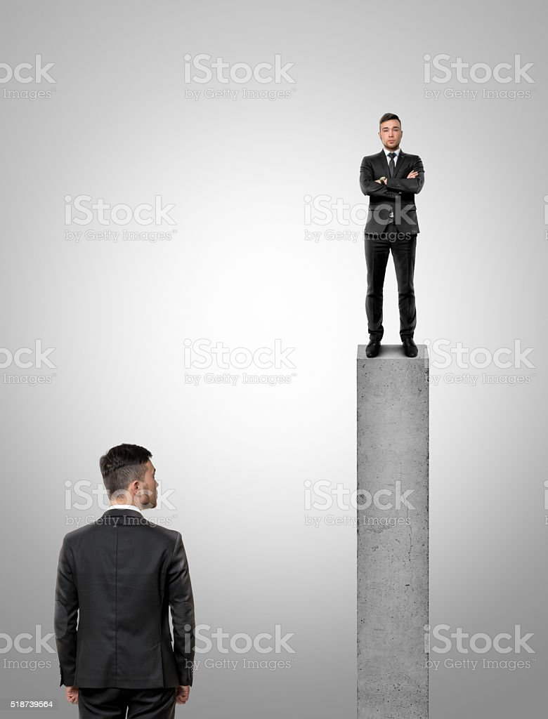 Businessman standing on peak of a concrete pillar looking at stock photo