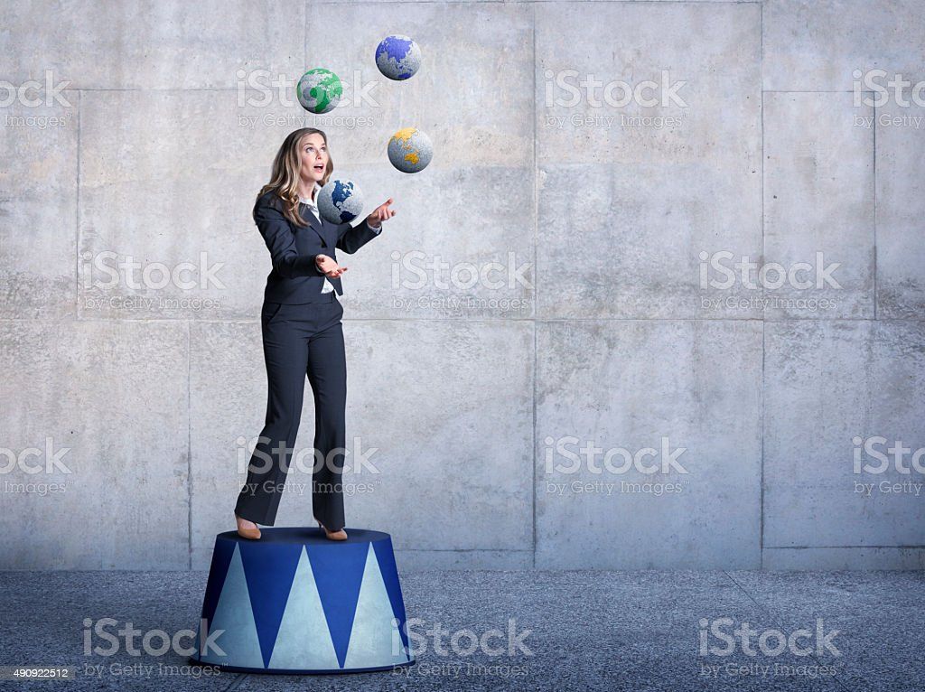 Businessman Standing On Pedestal Juggling Several Globes stock photo