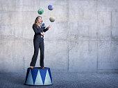 Businessman Standing On Pedestal Juggling Several Globes