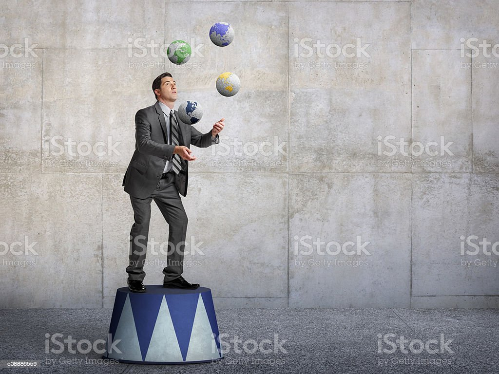 Businessman standing on pedestal juggling various globes of earth stock photo