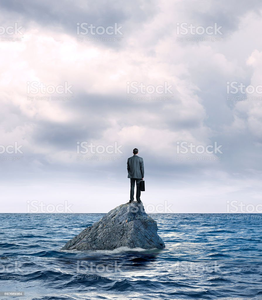 Businessman Standing On Rock In Middle Of Ocean stock photo