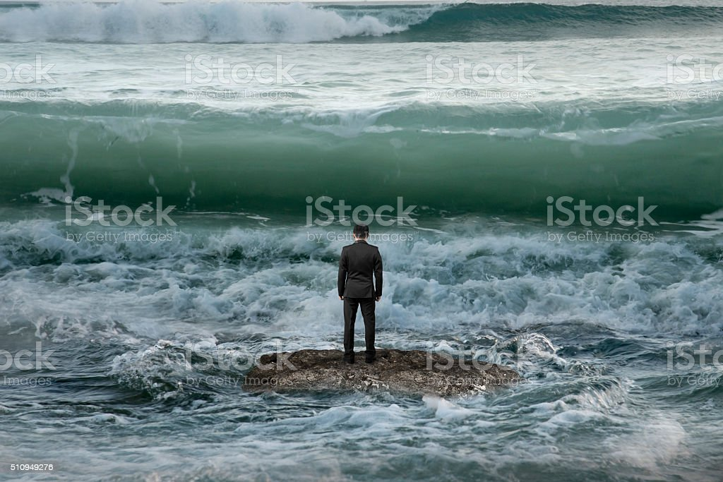 businessman standing on rock in the ocean facing oncoming waves stock photo
