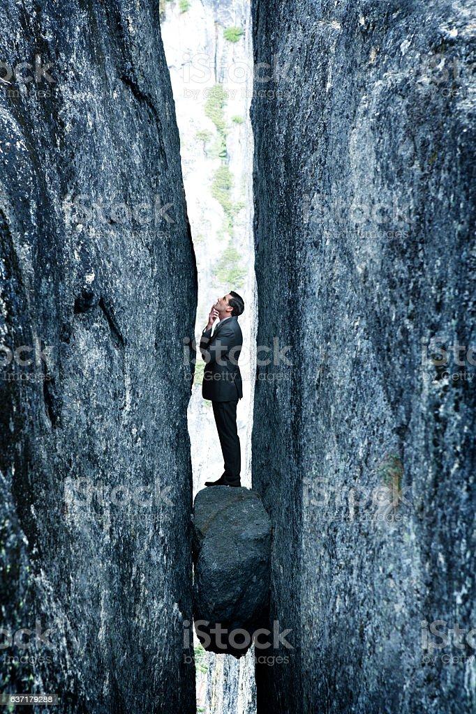 Businessman Standing On Rock Stuck In Deep Crevasse stock photo