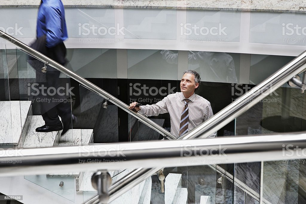Businessman standing on staircase stock photo