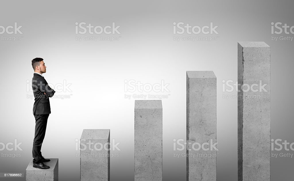 Businessman standing on the first of five columns with his stock photo