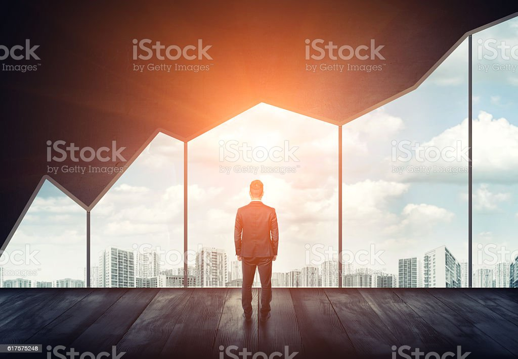 Businessman standing on the floor back to us looking through stock photo