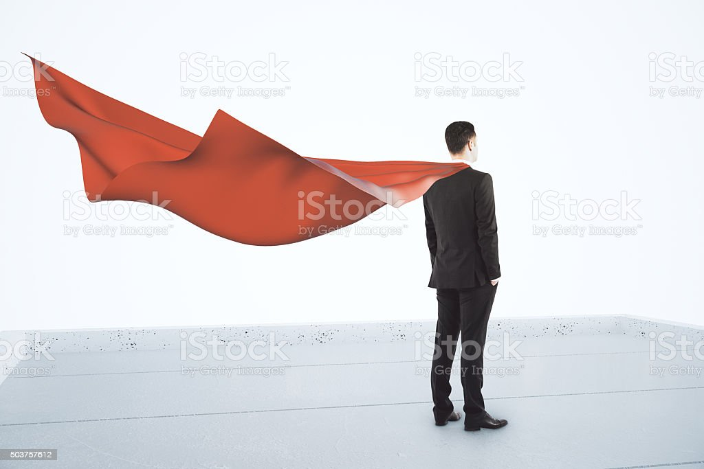 Businessman standing on the roof with a red cape stock photo