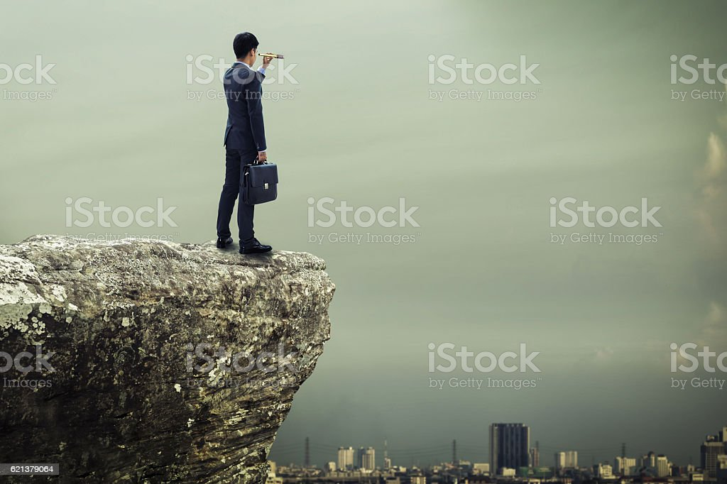 businessman standing on the top of mountain and searching stock photo