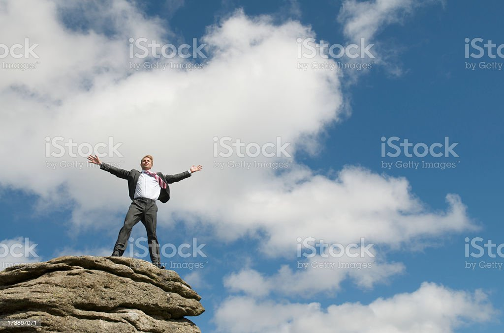Businessman Standing on Top of Rock Arms Spead Blue Sky stock photo