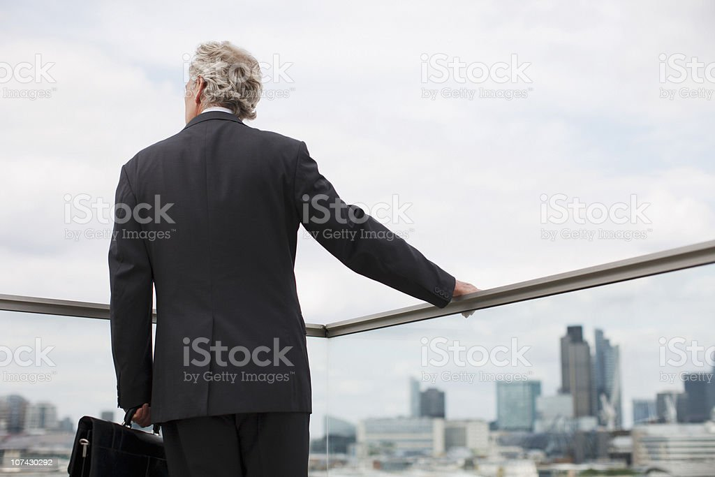 Businessman standing on urban balcony royalty-free stock photo