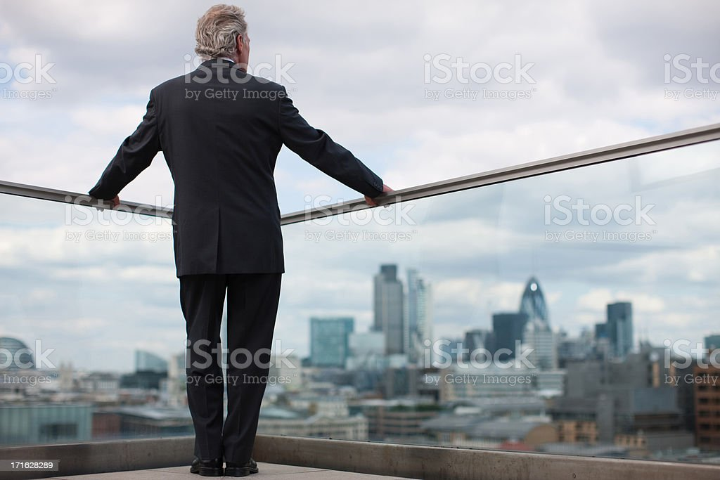 Businessman standing on urban balcony stock photo