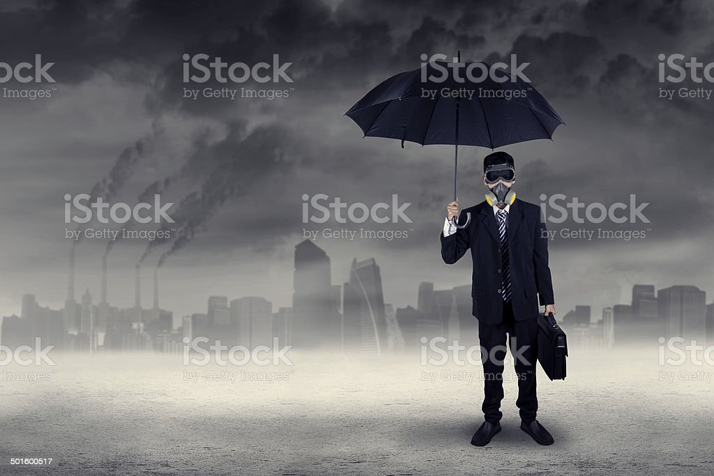 Businessman standing outdoors under air pollution stock photo
