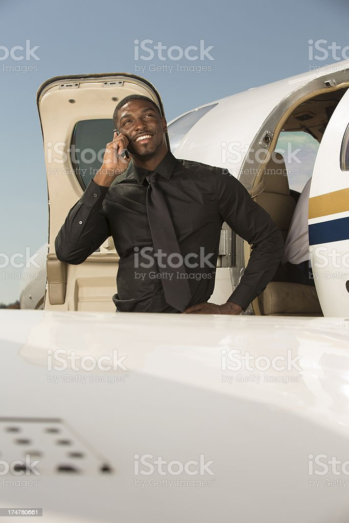 Businessman Standing Outside of Corporate Jet on the Phone royalty-free stock photo