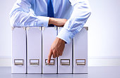 businessman standing over a folder with documents