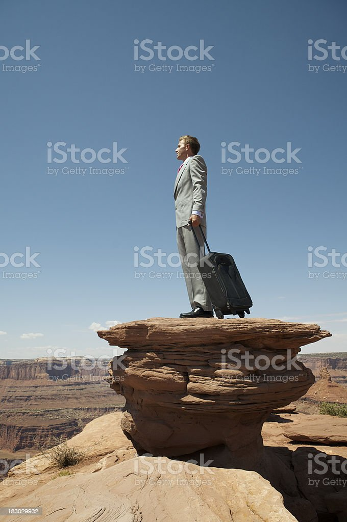 Businessman Standing Stranded on a Canyon Plateau stock photo