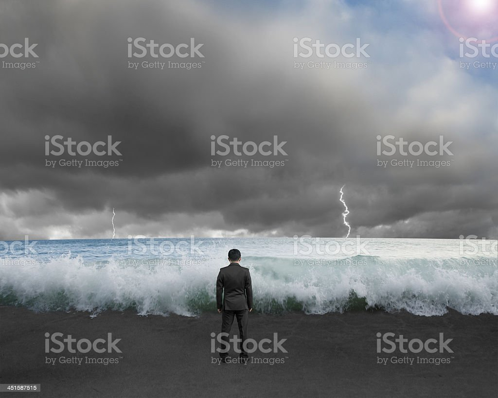 Businessman standing toward waves and cloudy sky with Lightning stock photo