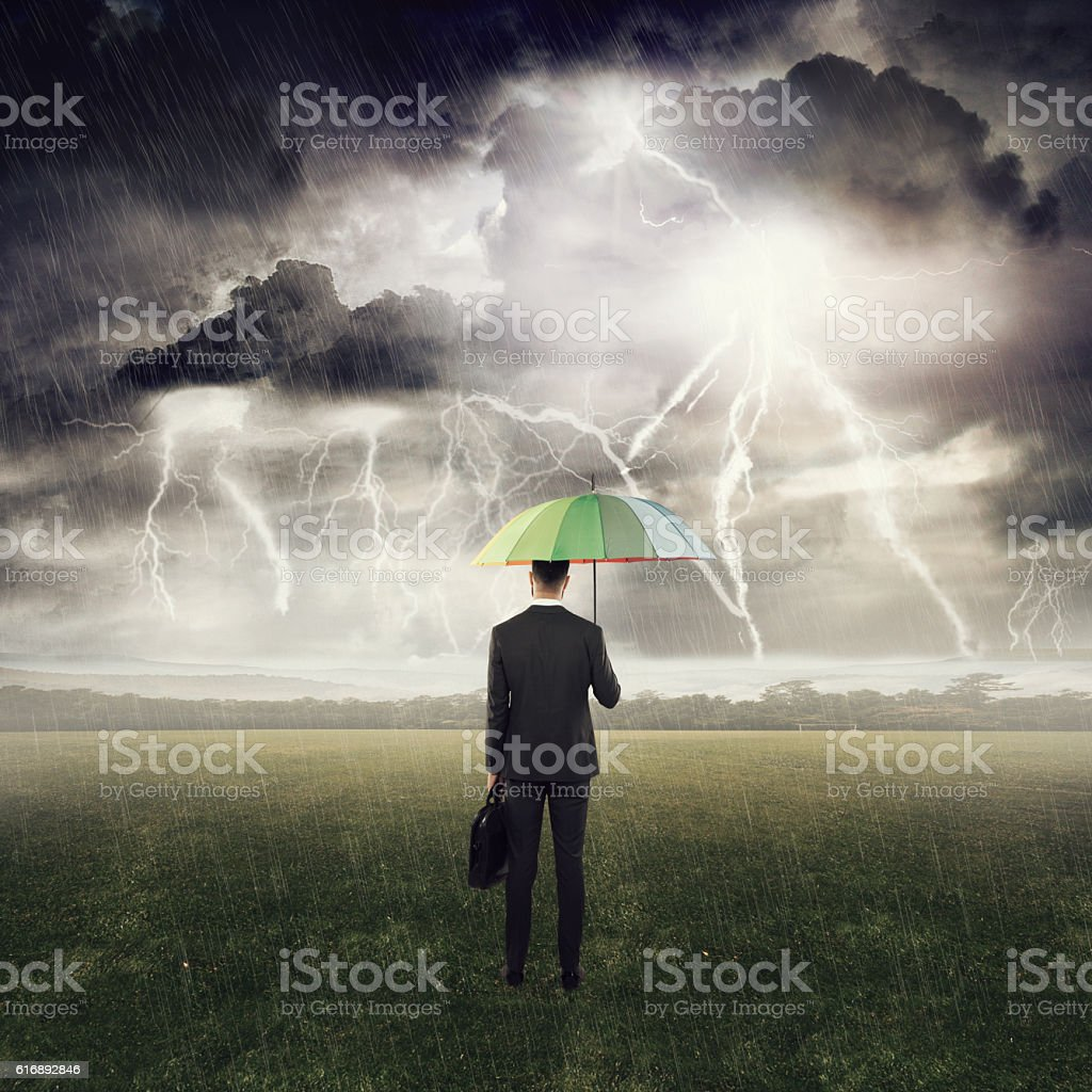 Businessman standing under an umbrella in field stock photo