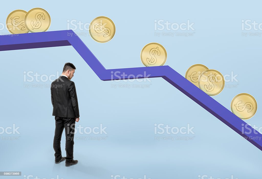 Businessman standing under falling graph with golden coins rolling down stock photo