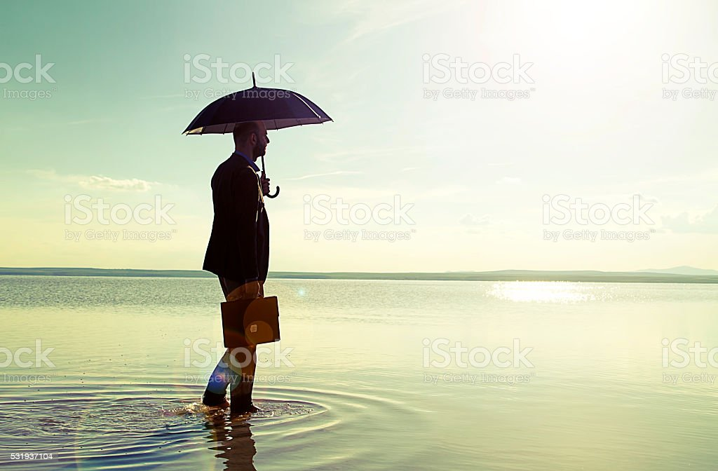 Businessman standing with a black umbrella On Salt Lake stock photo