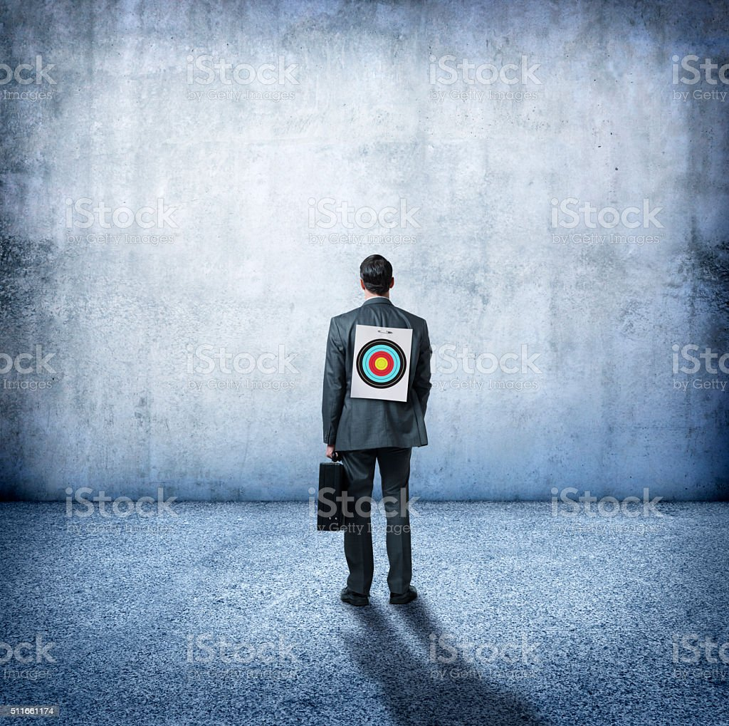 Businessman Standing With A Target On His Back stock photo