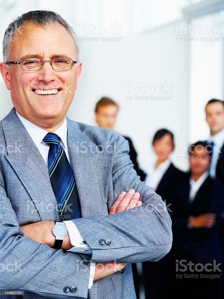 Businessman standing with arms crossed and smiling royalty-free stock photo