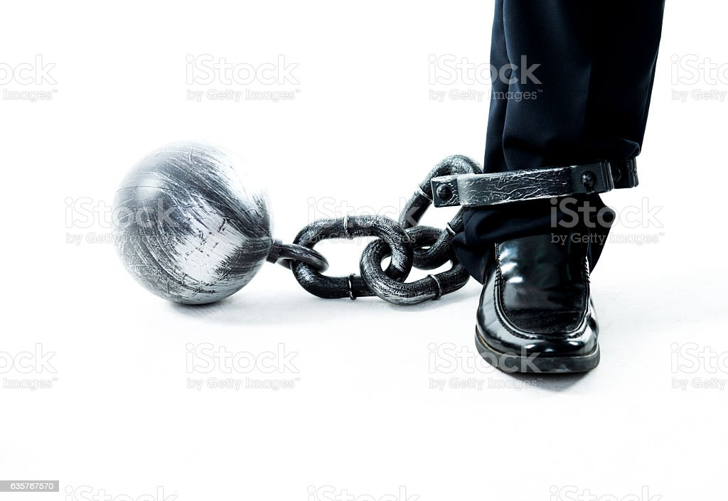Businessman standing with ball and chain stock photo