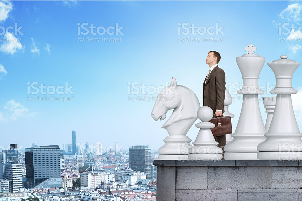 Businessman standing with big chess figures stock photo