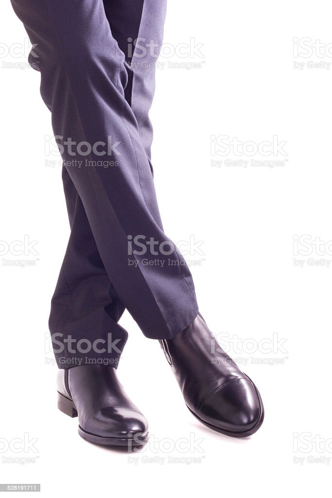 Businessman standing with crossed legs stock photo