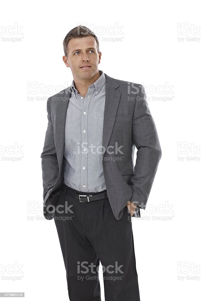 Businessman standing with hands in pockets stock photo