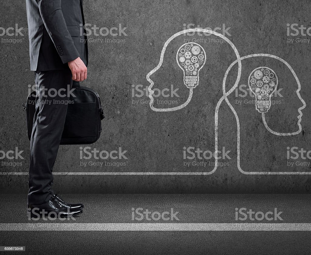 Businessman standing with human heads with light bulbs and gears stock photo