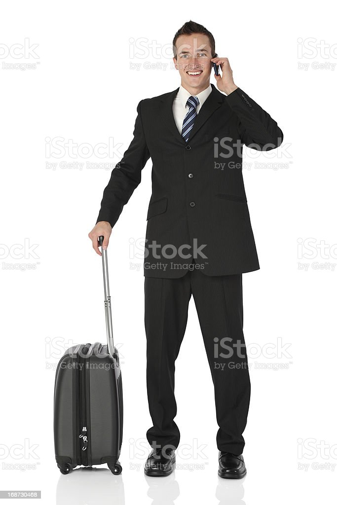Businessman standing with luggage talking on mobile phone royalty-free stock photo