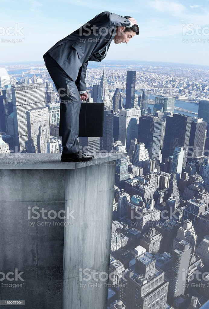 Businessman stands at edge of highrise looking down stock photo